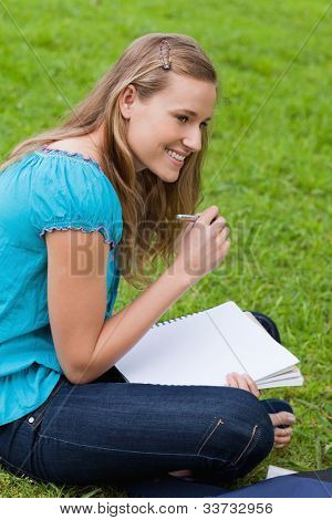 Smiling student looking towards the side while seriously writing on her notebook