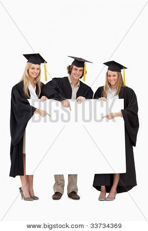 Three students in graduate robe holding and pointing a blank sign against white background