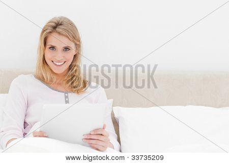 eine Frau hält einen TabletPC und Lächeln, als sie aufrecht im Bett sitzt.