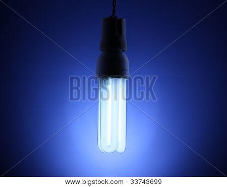A lit energy saving light bulb on blue background