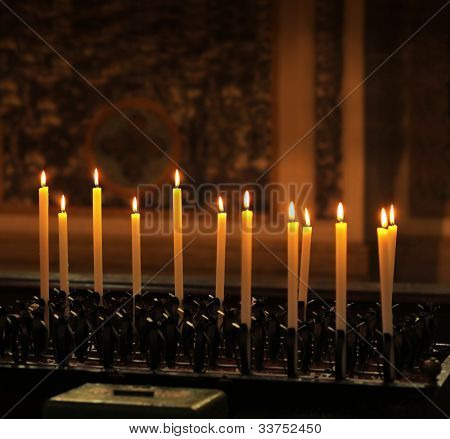 Row of tall lit candles  in a church with dark background