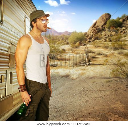 Sexy portrait of a man standing outside RV holding beer in beautiful setting