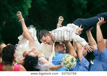 A happy groom and bride  tossed into air by a group of friends