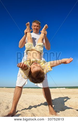 Boy flying on his parent 's hands at beach