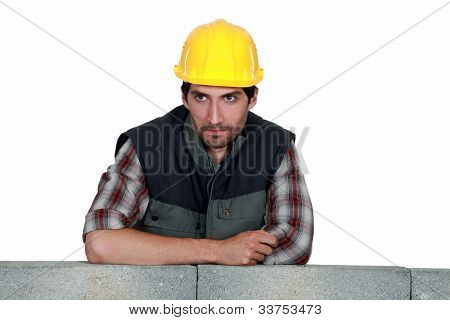 Builder leaning on wall