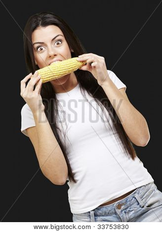 woman tasting a delicious corncob against a black background