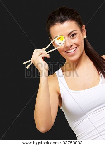 young woman covering her eye with a sushi piece against a black background