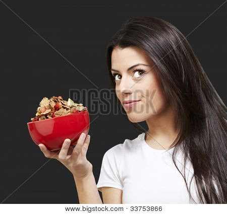 woman holding a delicious red breaksfast bowl against a black background