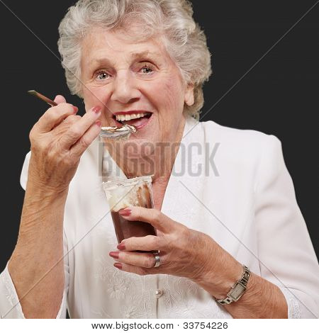 portrait of a senior woman eating chocolate and a cream cup over a black background