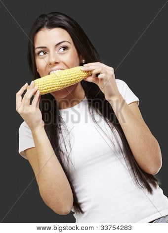 woman eating a delicious corncob against a black background