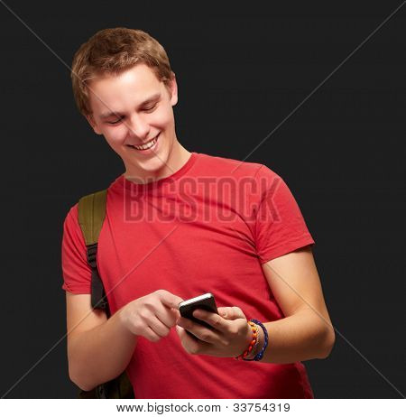 portrait of a young man touching a mobile screen over a black background
