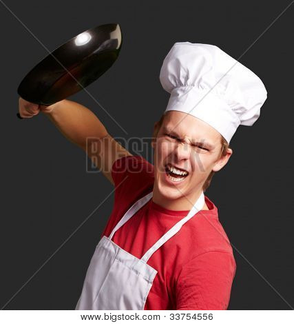 portrait of an angry young cook man hitting with a pan over a black background
