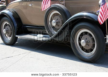 Antique car with American flags.