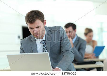 Vendedor en traje gris que asisten a la capacitación empresarial