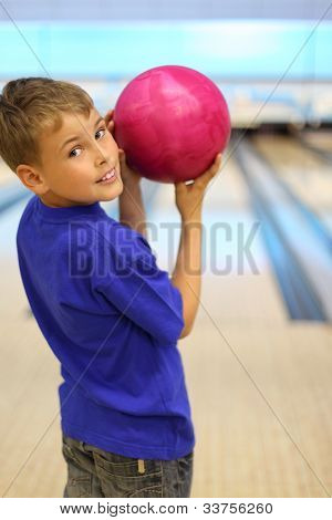 Smiling boy dressed in blue T-shirt holds pink ball in bowling club, stands with his back to camera and turns; shallow depth of field