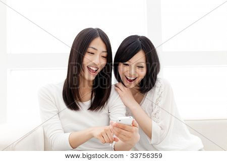 Beautiful young women using a moblie phone. Portrait of asian.