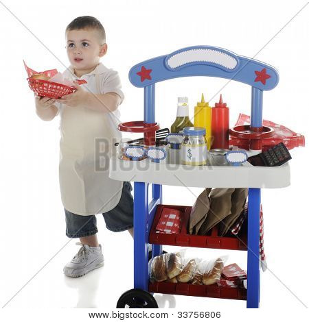An adorable preschooler passing out a basket of hot dog and chips from behind his vendor stand.  The stand's signs are left blank for your text.   On a white background.