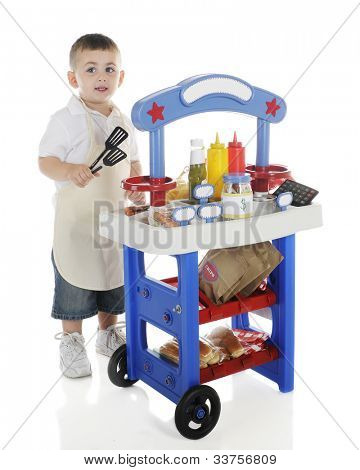 A young preschooler looking up as he tends his hot dog stand.  The stand's signs are left blank for your text.  On a white background.