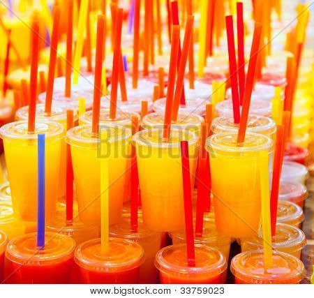 Colorful natural fresh fruits juice glasses with straw stacked in rows