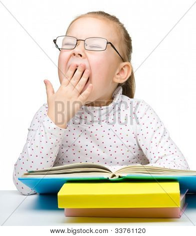 Cute cheerful little girl yawning while reading book and wearing glasses, isolated over white
