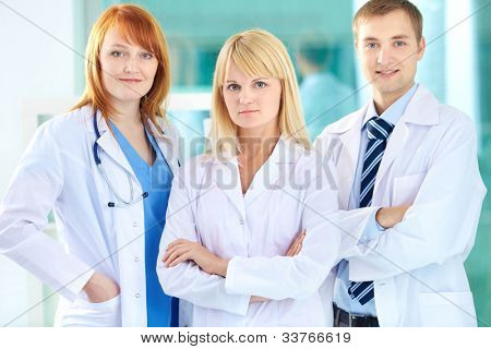 Portrait of three clinicians in white coats looking at camera