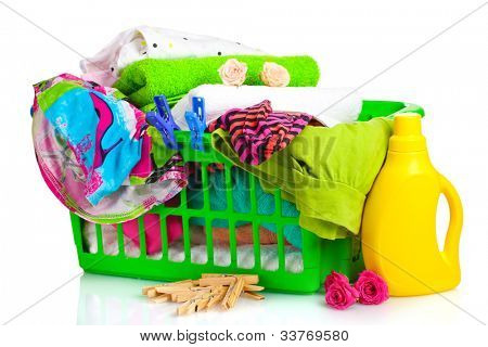 Clothes with detergent and in green plastic basket isolated on white