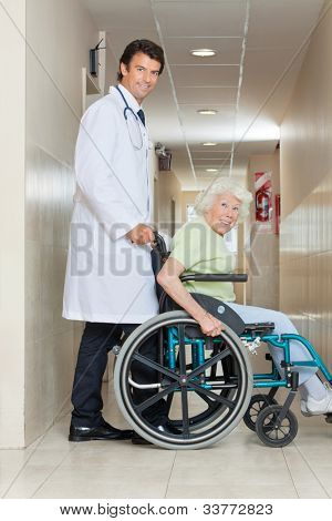 Side view of a happy young doctor assisting senior woman sitting in a wheel chair