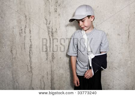 Boy with arm in a sling from a broken humerus wearing a baseball