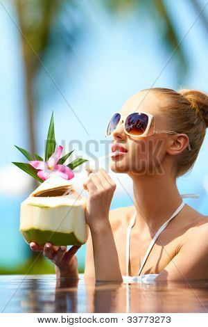 Woman soaking in a pool in her bikini and sunglasses sipping a tropical cocktail through a straw