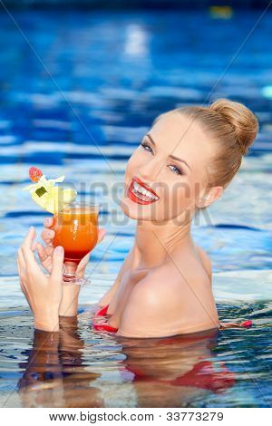 Pretty blonde girl with a big smile holding a tropical drink while standing in a swimming pool