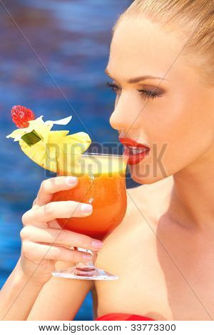 Cropped view image of the face of a beautiful woman sipping a large colourful tropical cocktail