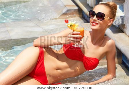 Sweet smile on a gorgeous blonde woman in a small bikini holding a tropical drink in her hand while laying poolside