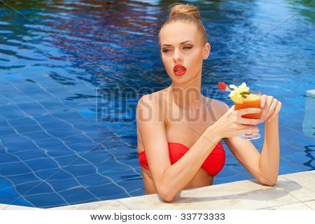 Beautiful blonde woman in a red bikini standing in a pool with a tropical cocktail