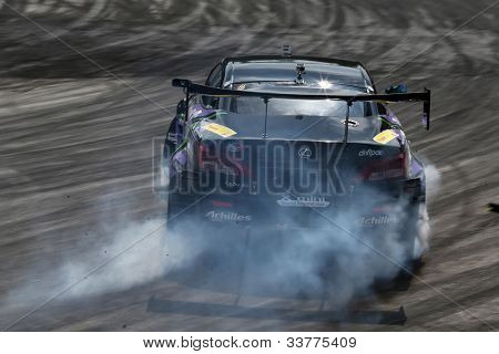 KUALA LUMPUR - MAY 19: Japan's drift champion Daigo Saito in a Lexus SC430 throw gravel and smoke during a practice run at the Formula Drift 2012 Asia Round 1 on May 19, 2012 in Speedcity, Malaysia.