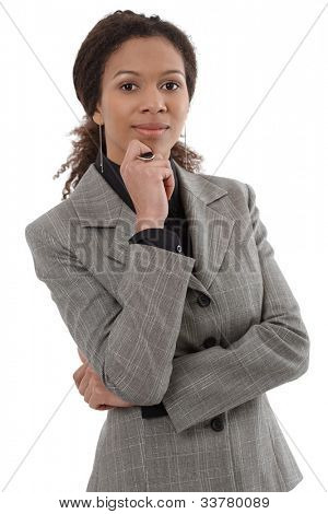 Portrait of smart ethnic businesswoman standing with hand on chin.