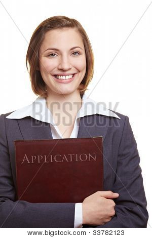 Smiling female applicant holding application folder in her hands