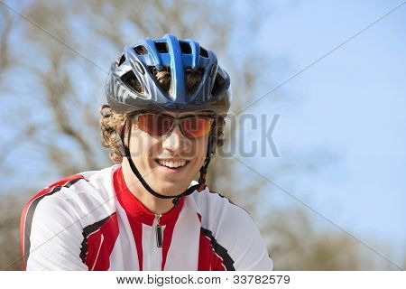 Happy bicyclist wearing goggles and crash helmet