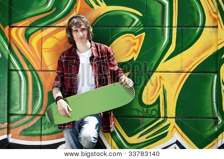 Young man listening music near a graffiti wall and holding skateboard
