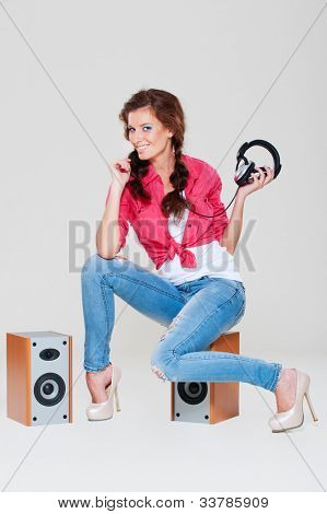 studio shot of smiley woman sitting on speakers over grey background