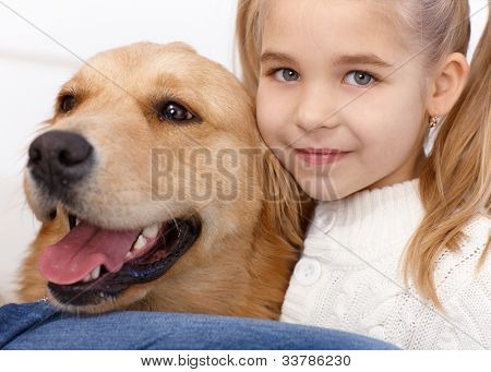 Closeup portrait of lovely little girl and golden retriever, hugging, smiling.