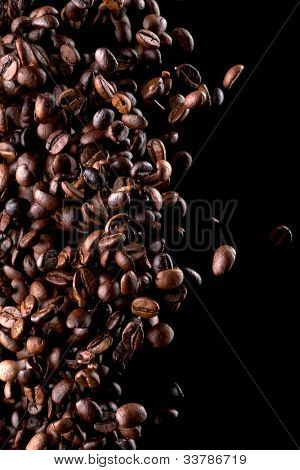 Flying coffee beans over dark
