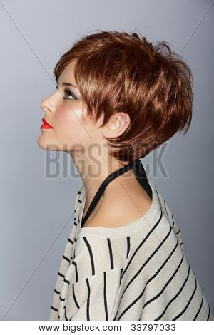 profile of a beautiful woman with red lips and short feathered red hair in modern bob over studio background
