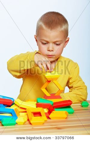 little 3 year old toddler boy playing with bright plastic pyramid blocks over light studio background.