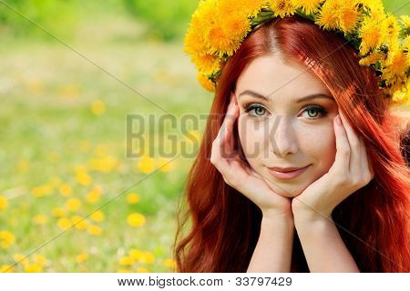 Romantic young woman in a circlet of flowers outdoors.