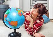 Young girl student study geography with globe planet Earth in interior room. poster