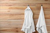 Soft Comfortable Bathrobe And Towel Hanging On Wooden Wall. Space For Text poster