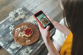 Cropped View Of Young Adult Food Stylist Using Modern Smartphone, Making Photo With Dessert And Crea poster