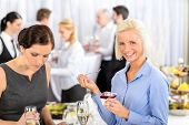 stock photo of party people  - Business meeting buffet smiling woman eat dessert formal company event - JPG