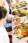 stock photo of banquet  - Business people around buffet table catering food at company event - JPG