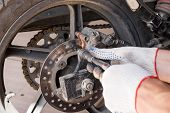 The Process Of Replacing Brake Pads On A Motorcycle. poster